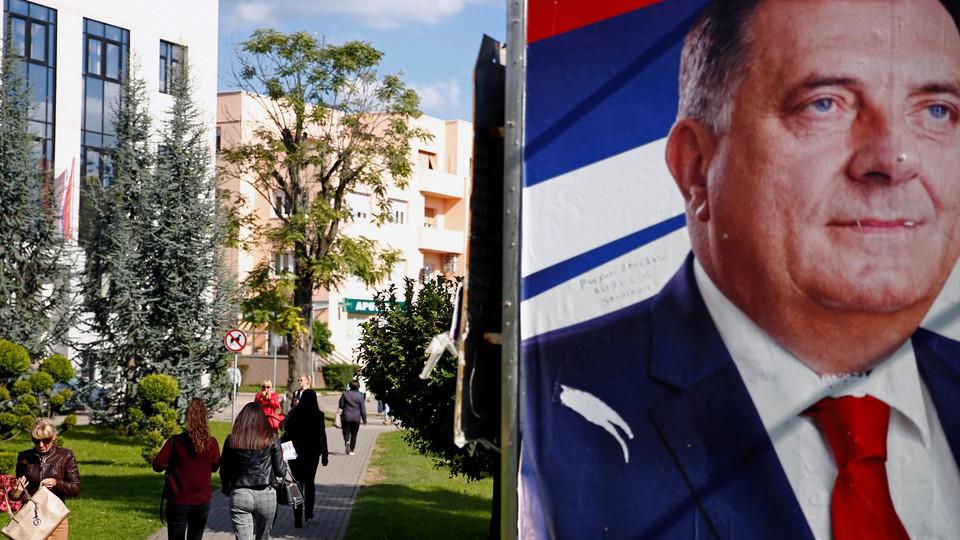 People walk by a Dodik campaign billboard in Banja Luka in September.