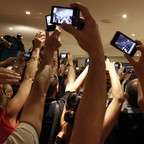 Journalists with cell phones and cameras taking pictures.