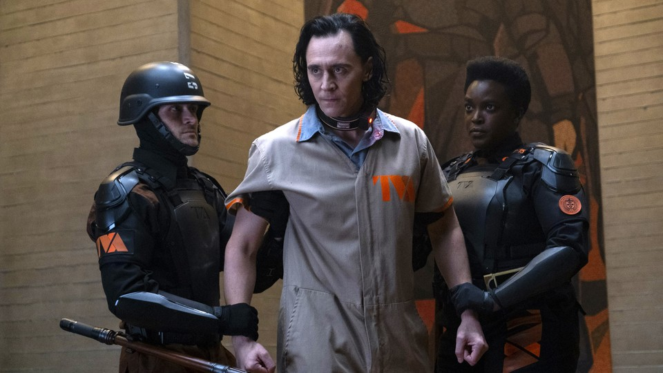 Loki restrained by two guards from the TVA
