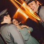 Two men, dressed in military uniforms, chat with a woman in a flowy dress and pearls.