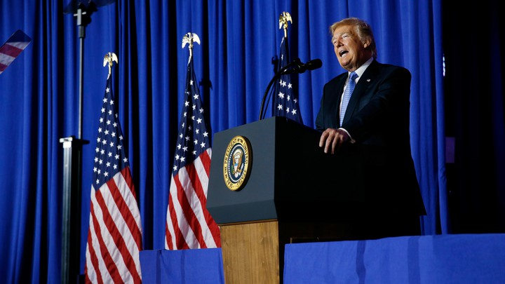 President Donald Trump delivers a speech in front of U.S. flags.