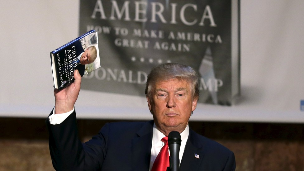 """Donald Trump holding up a copy of his book """"Crippled America"""""""