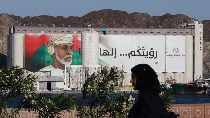 A woman walking past portrait of Sultan Qaboos