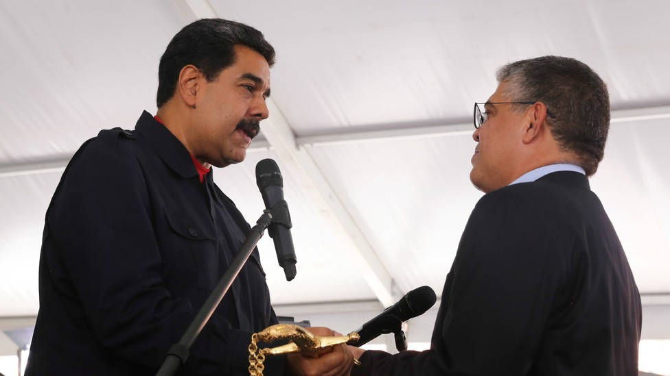 Maduro presents Minister for Education Elias Jaua with a replica of the sword of national hero Simon Bolivar during a ceremony in Caracas on July 26, 2017.
