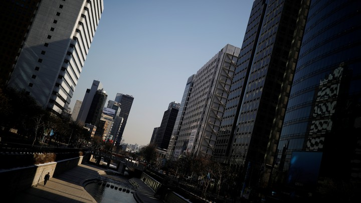 A man walks along a canal next to skyscrapers