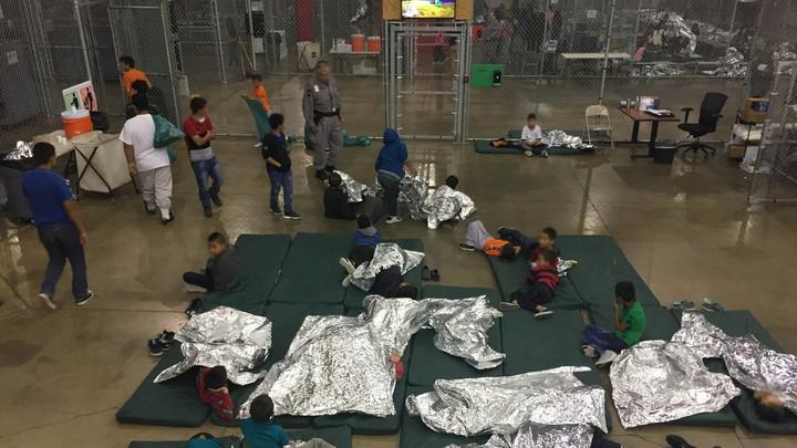 Kids lie on mats, some under foil sheets, on a floor in a detention-center pen.