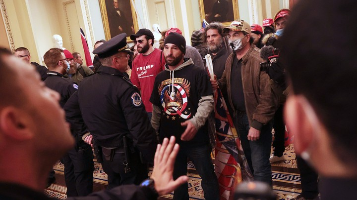 Insurrectionists inside the Capitol building, confronted by police. Man in center is wearing a QAnon T-shirt.