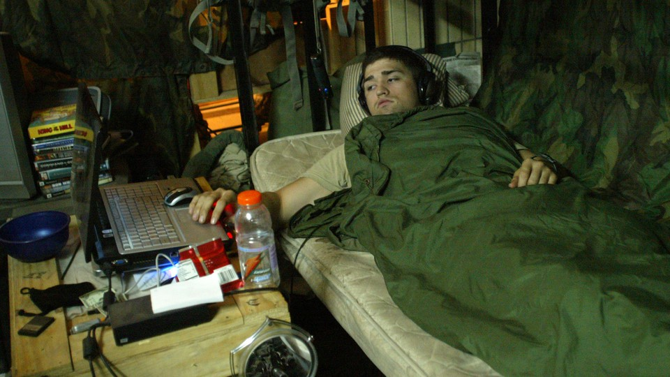 A man watches a movie on his laptop while wearing headphones and lying on a bed with camouflage bedding.
