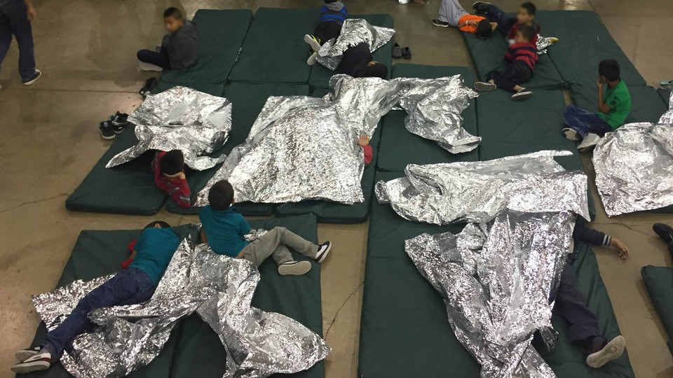 Children lie on green mattresses on the floor and use silver space blankets.