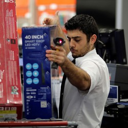 An employee scans televisions on Black Friday.