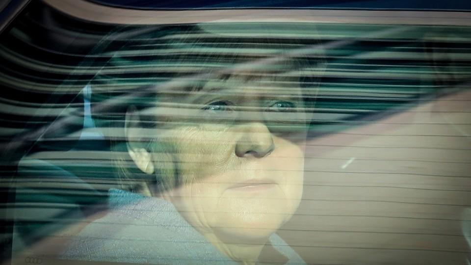 Angela Merkel stares out a car window.