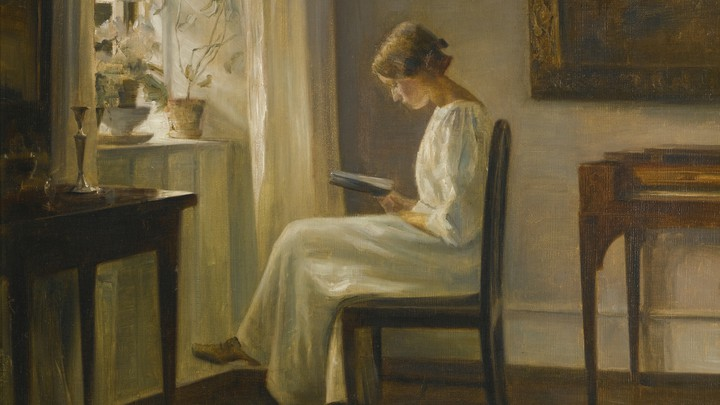 A woman reads next to a window