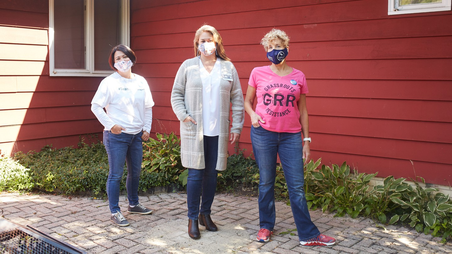 GRR's leader, Susan Polakoff Shaw, stands with two other women wearing jeans outside a red wood-paneled house.