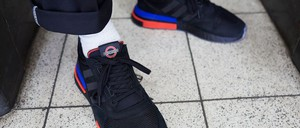 A pair of black, London Underground-themed Adidas sneakers with red and blue trim.
