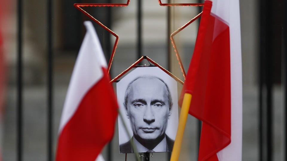 A photo of Russian President Vladimir Putin between two Polish flags