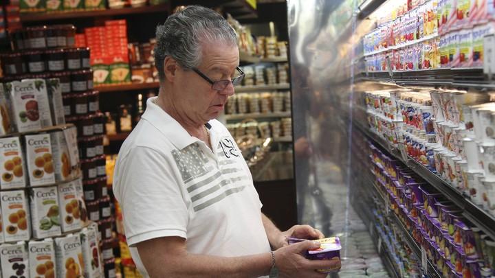 An elderly man shops for groceries