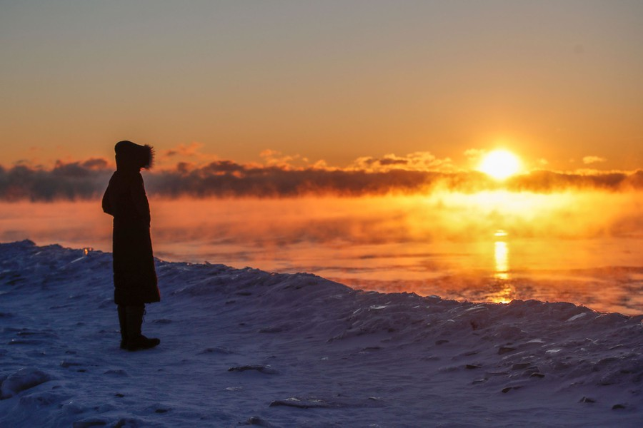 A person stands on a frozen lake shore at sunrise.