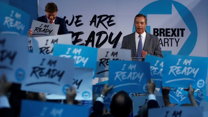 "Nigel Farage speaks to Brexit Party supporters who hold signs reading ""I am ready."""