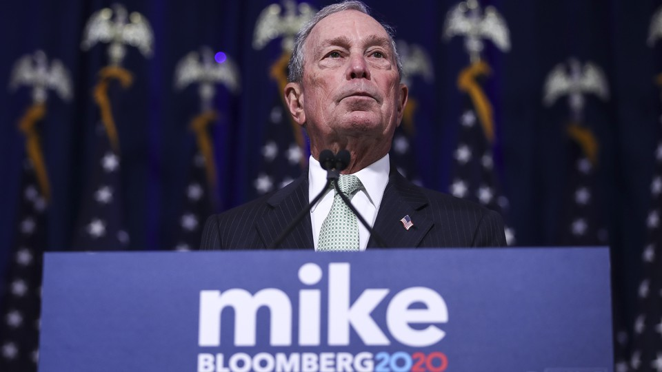 Michael Bloomberg stands at a lecturn.