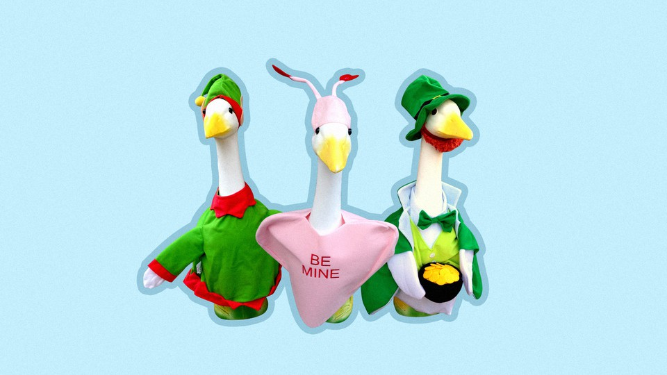 """Three statues of geese, dressed in an elf outfit, a heart that says """"be mine"""" and a leprechaun outfit"""