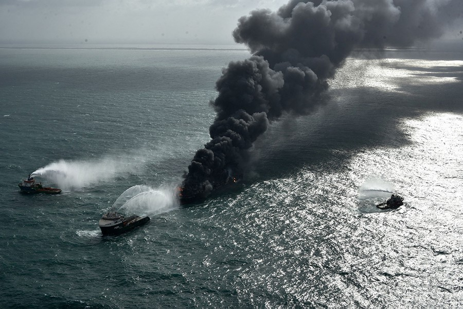 Several fireboats work to extinguish a burning ship, with black smoke rising into the sky.