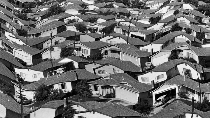 A warped black and white photograph of rows of houses in a neighborhood