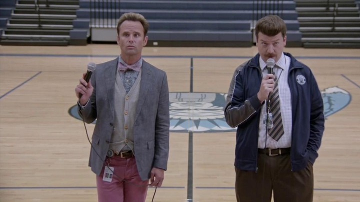 Walton Goggins, as Lee Russell, and Danny McBride, as Neal Gamby, stand in the center of a gymnasium holding microphones.