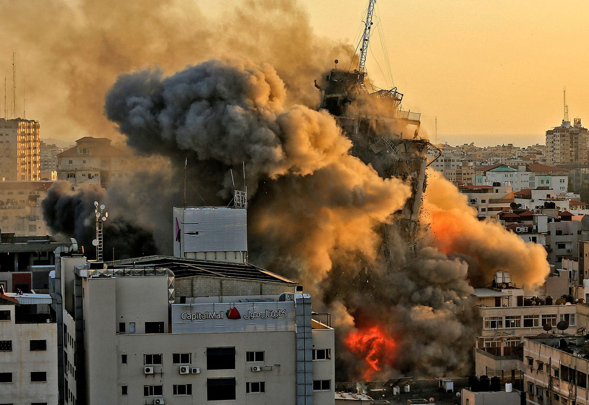 Smoke, dust, and fire erupt around a multistory tower as it collapses amid many other buildings.