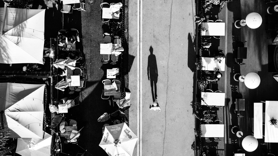 A pedestrian walks down a city street repurposed for outdoor dining.