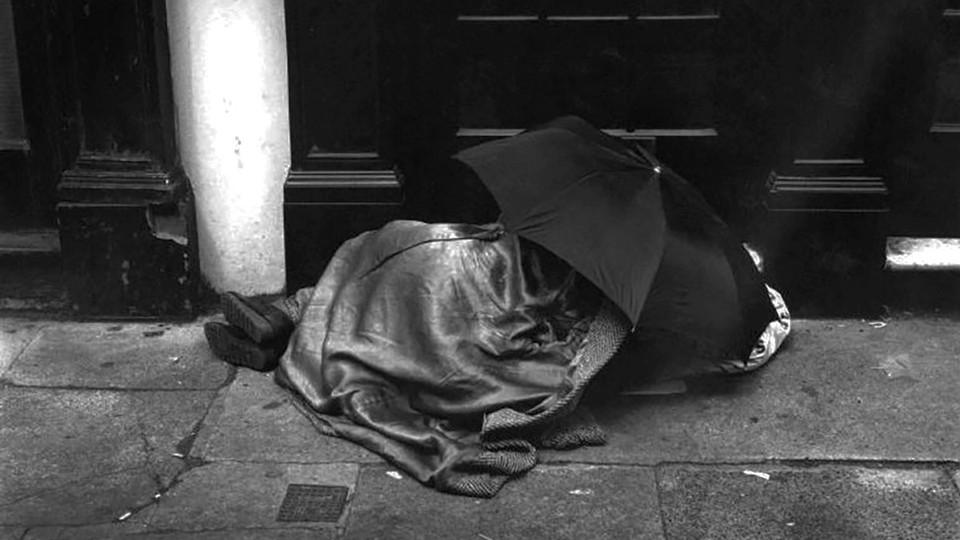 An unsheltered person sleeping under an umbrella in London