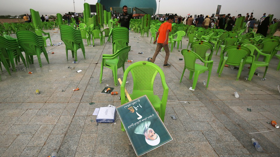 A field of empty chairs with a discarded campaign poster