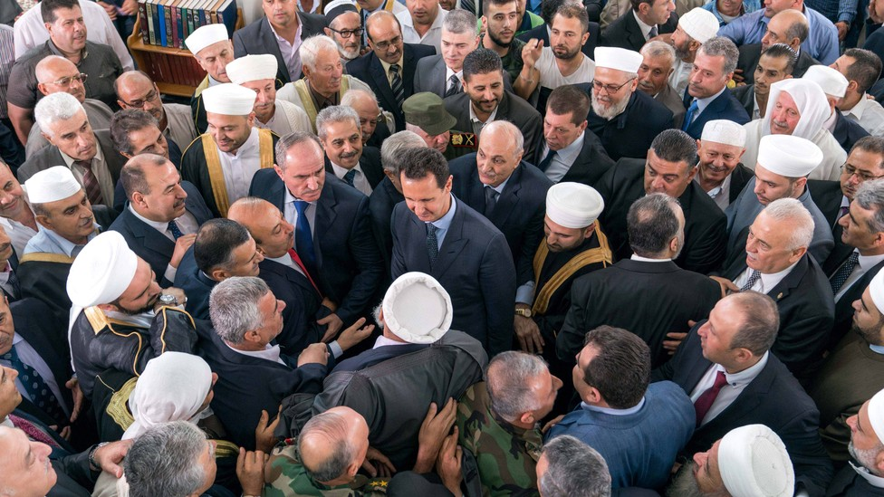 Assad stands in the middle of a throng of supporters, who greet him after Eid al-Fitr prayers at a mosque in Tartous.