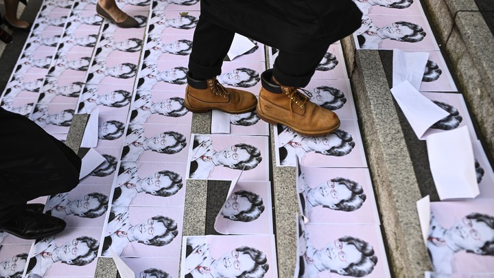 People walk over pictures of Hong Kong's chief executive, Carrie Lam.