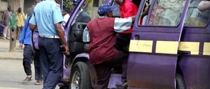 A policeman boards a matatu in Nairobi.