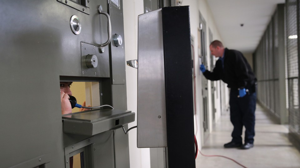 """An immigrant detainee makes a call from his """"segregation cell"""" at the Adelanto Detention Center"""