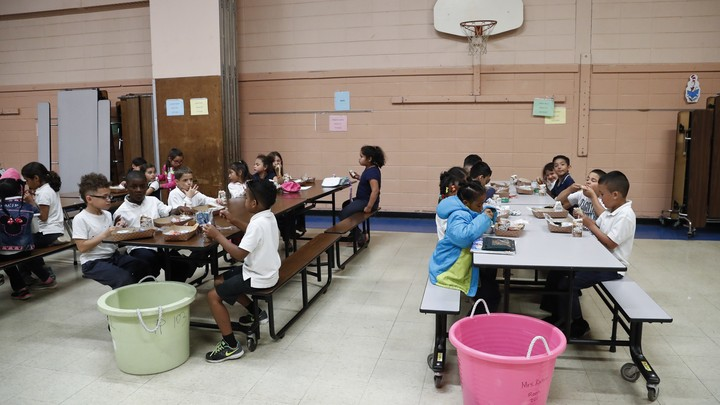 A group of children eats at two long lunch tables.