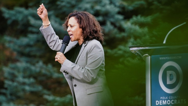 California Senator Kamala Harris speaks to a crowd with her arm raised at Polk County Democrats' Steak Fry in Des Moines, Iowa in September.