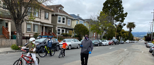 """photo: A family walks down West 19th Street in Oakland, part of the city's """"slow streets"""" network."""