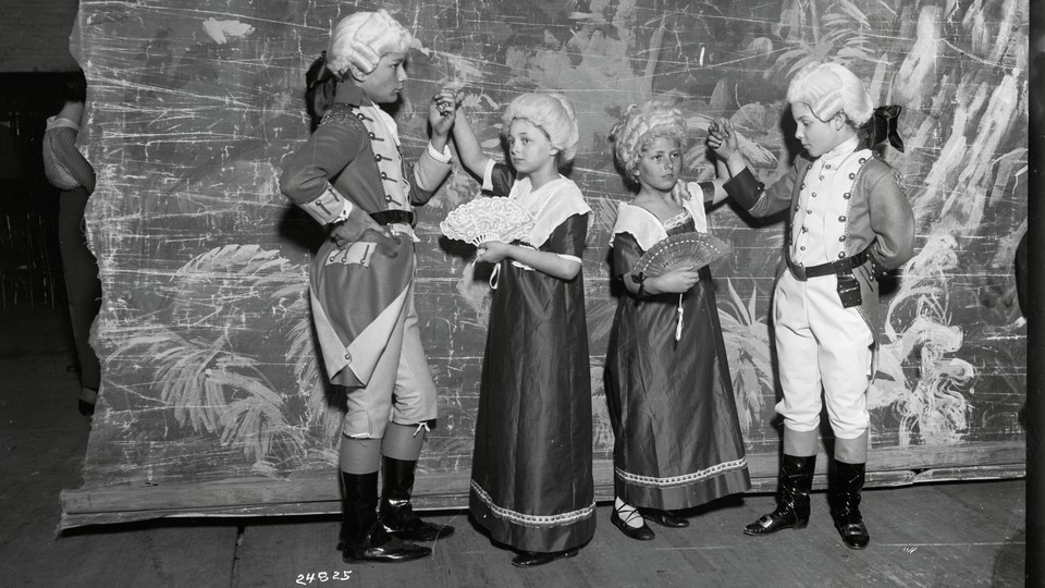 Children in colonial-era costumes on a theater stage.