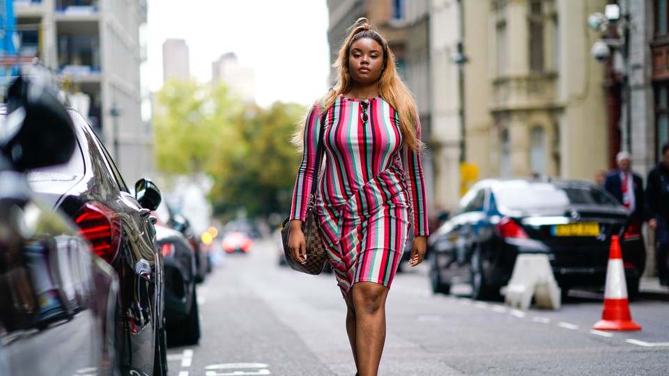 A woman in a fashionable striped dress walks down the street.