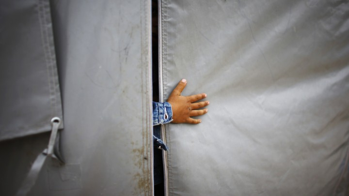 A refugee boy from the Syrian town of Kobani sticks his hand out of a tent in a refugee camp.