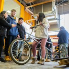 A group of students talk as one tests a pedal-free bicycle they have built.