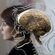 A woman sits besides a real human brain, displayed in Bristol, England.