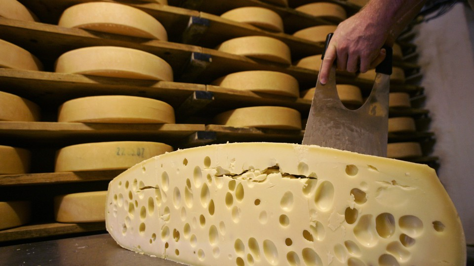 A hand slices cheese in front of shelves of more cheese.