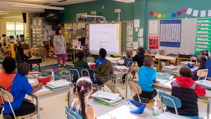 First-grade students are seated in a classroom listening to their teacher.