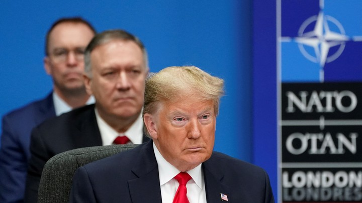Donald Trump, Mike Pompeo, and Mick Mulvaney sit in a line while attending a NATO summit.