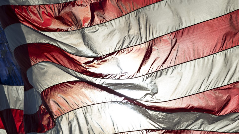 An American flag backlit with sunlight