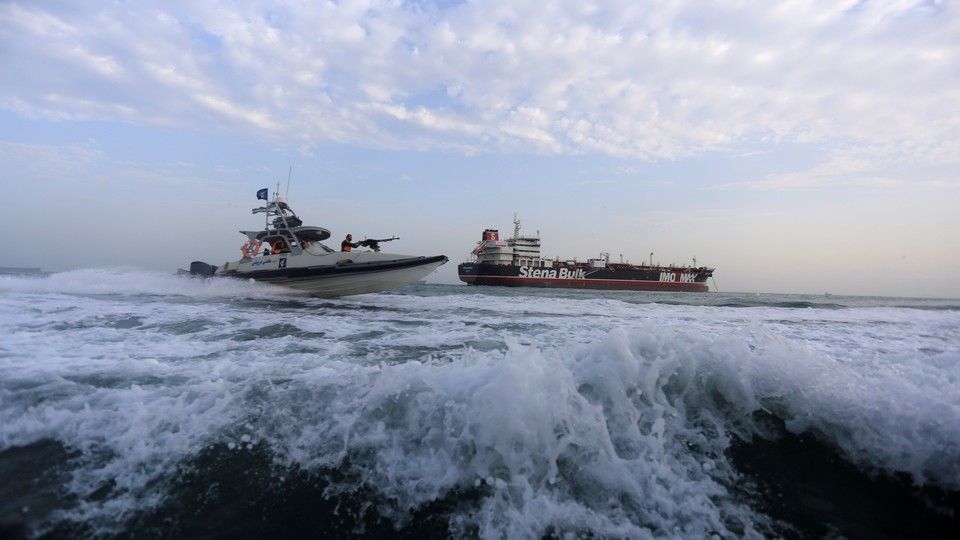 A military speedboat sails close to a tanker.