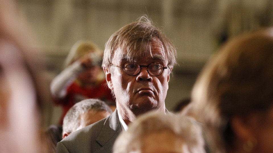 Garrison Keillor listens to U.S. President Barack Obama speak at a campaign rally in Minneapolis, Minnesota October 23, 2010.