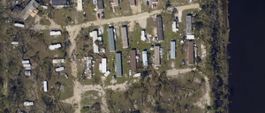Aerial view of mobile homes damaged by a hurricane.